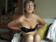 This 50-something mama takes off her brassiere and shows us her tits, squeezing them, profiling them, lifting 'em and playing with her nipples.