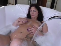 Mature in a soapy bathtub masturbates solo